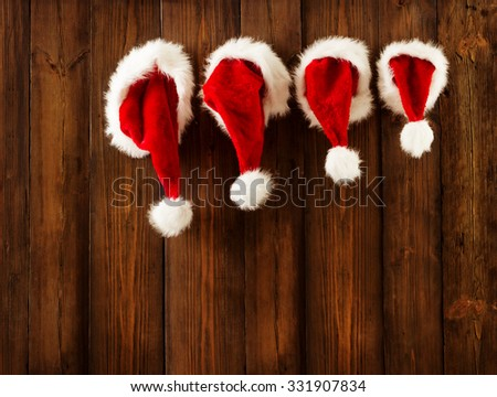 Christmas Family Santa Claus Hats Hanging on Wood Wall, Xmas Kid Hat Hang on Decorated Background - stock photo