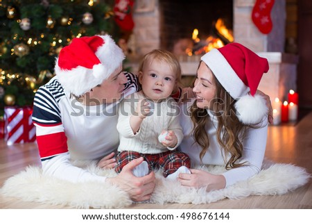 Christmas family sitting on floor in home holiday living room