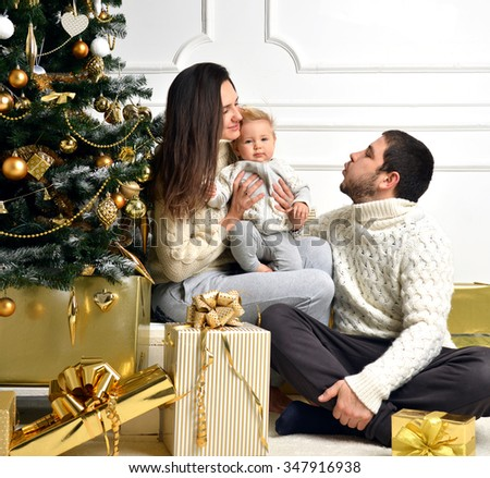 Christmas Family with baby Kid and gold present gifts. Happy young Parents and Child at Home Celebrating New Year. Christmas Tree. Christmas scene - stock photo