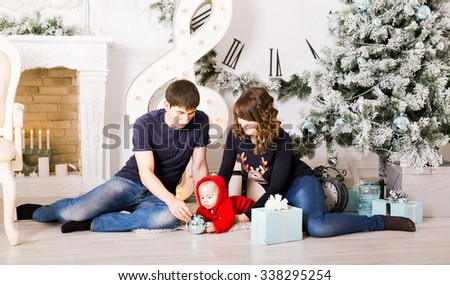 Christmas Family with baby opening gifts. Happy Smiling Parents and Child at Home Celebrating New Year - stock photo