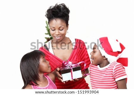 Christmas family with focus on mom holding gift-box and two curious kids watching - stock photo