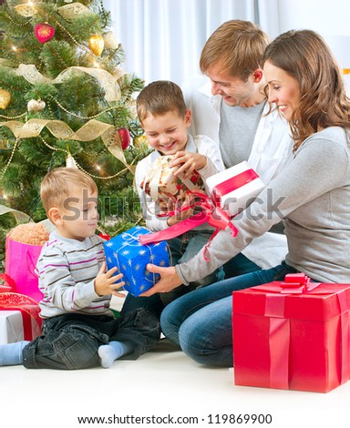 Christmas Family with Kids. Happy Children Opening Gift. Christmas tree