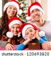 Christmas Family with Kids. Happy Smiling Parents and Children at home. Christmas Tree. Santa Hat - stock photo