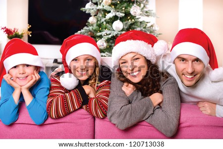 Christmas Family with Kids. Happy Smiling Parents and Children at home. Christmas Tree. Santa Hat. Father,mother,sister and brother Celebrating New Year together - stock photo