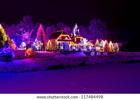 Christmas fantasy - park, forest, pine tree & lodge in xmas lights - stock photo