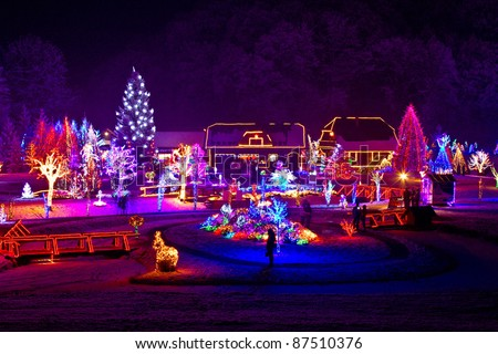 Christmas fantasy - trees and houses in lights on beautiful snowy winter night - stock photo