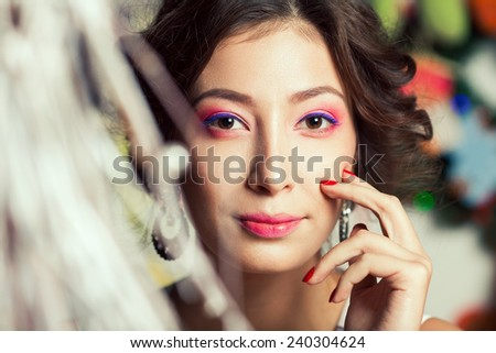 Christmas fashion beauty concept. Portrait of young brunette with arty make-up wearing luxurious vintage diamond earrings and posing over christmas tree background. Retro style. Close up. Indoor shot - stock photo