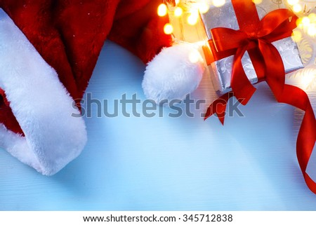Christmas  festive background with  gift box and hat of Santa Claus - stock photo