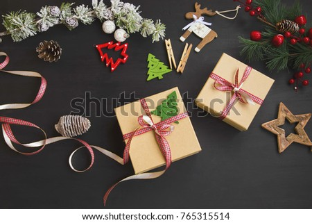 Christmas festive presents with red ribbon and decorations on wooden background, top view