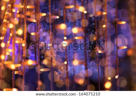 Christmas festoon blurred lights background with orange and violet colors - stock photo