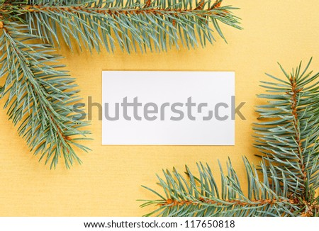 Christmas fir branches framework and empty card on yellow background - stock photo