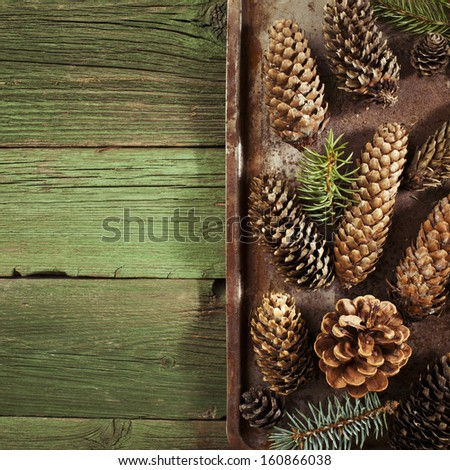 Christmas fir cones on vintage green wooden background - stock photo