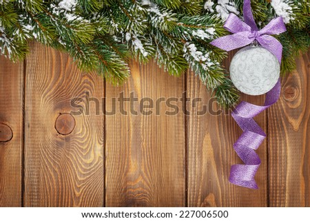 Christmas fir tree and bauble with purple ribbon on rustic wooden board with copy space - stock photo