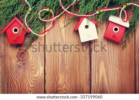 Christmas fir tree and birdhouse decor on rustic wooden board with copy space. Toned - stock photo