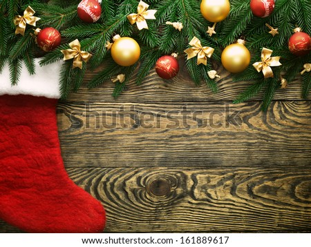 Christmas fir tree and christmas sock with decoration on a wooden board