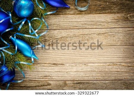 Christmas fir tree branch with decorations on an old wooden plank, copy space for text, top view.