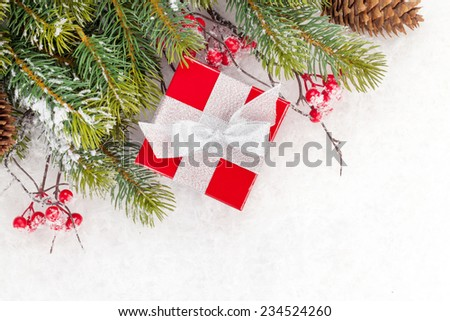 Christmas fir tree branch with holly berry and gift box over snow - stock photo