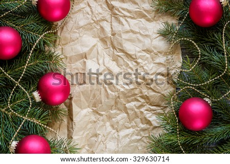 Christmas fir tree branches decorated with red balls frame an old paper, copy space for text, top view.