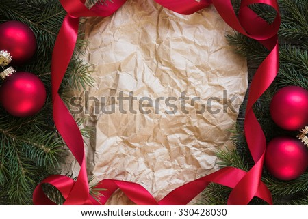 Christmas fir tree branches, red ribbon and Christmas balls frame an old paper, copy space for text, top view.