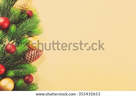 Christmas fir tree branches with toys on paper background