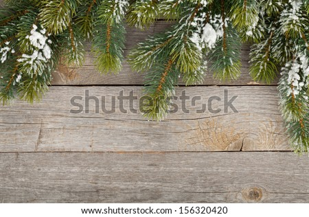 Christmas fir tree covered with snow on wooden board background - stock photo