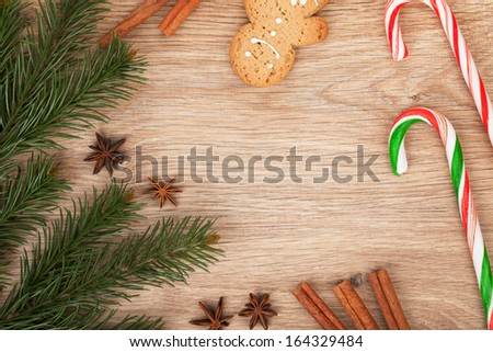 Christmas fir tree, gingerbread cookie and candy cane on wooden background - stock photo