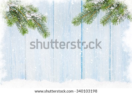 Christmas fir tree in snow in front of wooden wall. View with copy space - stock photo
