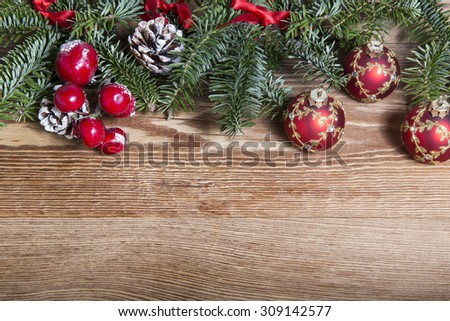 Christmas fir tree with baubles on rustic wooden board with copy space