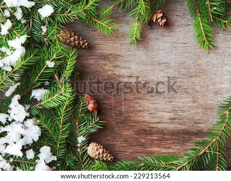 Christmas fir tree with cones and snow on a wooden background, selective focus and place for text. Toned  - stock photo