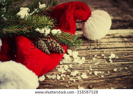 Christmas fir tree with cones,christmas red hat and snow on a wooden background/ Christmas background