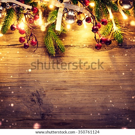 Christmas fir tree with decoration on dark wooden board background. Border art design with Christmas tree, baubles and light garland - stock photo