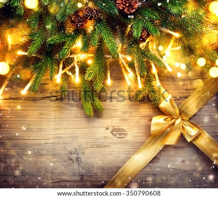 Christmas fir tree with decoration on dark wooden board background. Border art design with Christmas tree, baubles, light garland and golden gift ribbon with bow - stock photo