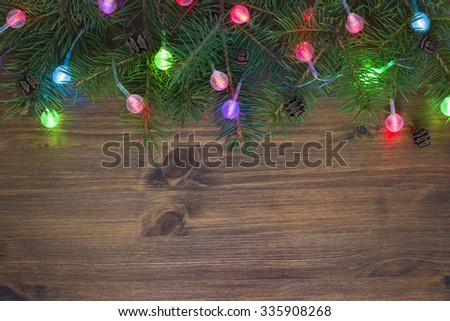 Christmas fir tree with lights on wooden background - stock photo