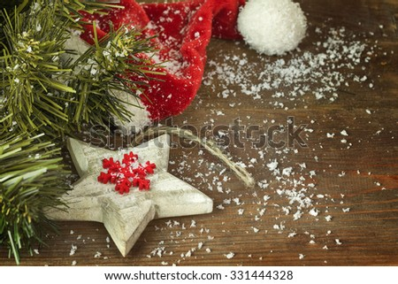 Christmas fir tree with  red hat and snow on a wooden background
