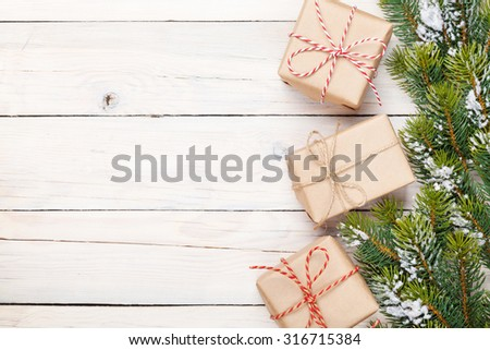 Christmas fir tree with snow and gift boxes on rustic wooden board with copy space - stock photo