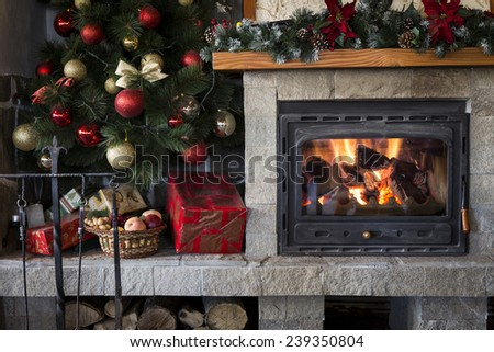 Christmas fireplace and tree decorated with baubles - stock photo