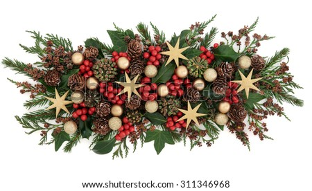 Christmas floral display with star and gold baubles, holly, mistletoe, ivy and winter greenery over white background. - stock photo