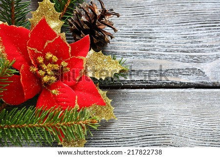 Christmas flower red with bows on a wooden board, close up - stock photo
