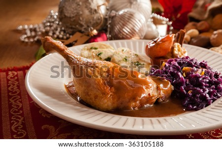 Christmas food close up of roast chicken drumsticks and some xmas baubles in the background - stock photo