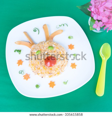 Christmas food for kid, Fried rice with egg in the shape of reindeer, with antler made from sausage, decorated with vegetables, on a white plate