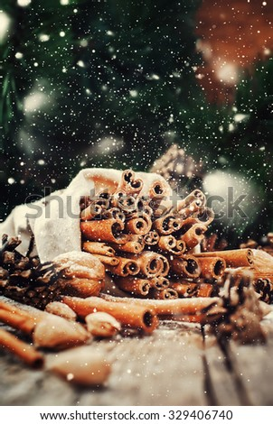 Christmas Food on Wooden Background. Sticks of Cinnamon in Linen Bag, Pine cones, Walnuts. Toned. Drawn snow - stock photo
