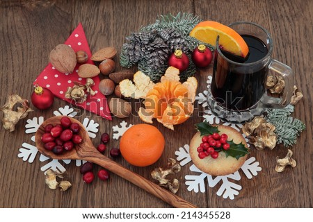 Christmas food with mulled wine ingredients of citrus fruit and spices with nuts and mince pie over oak background.