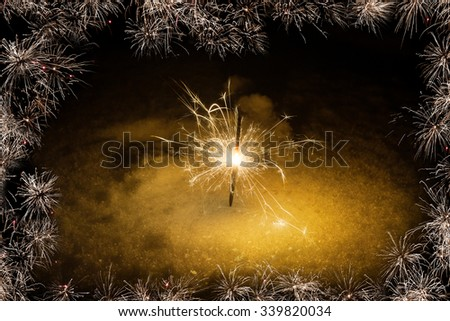 Christmas frame and sparkler surrounded by sparks - stock photo
