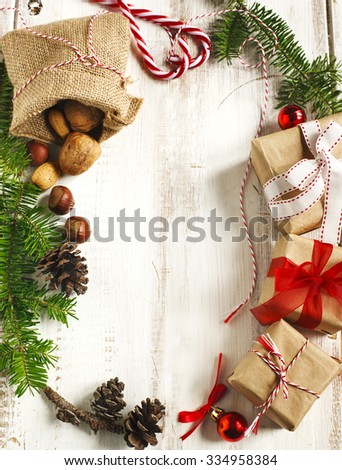 Christmas frame. Christmas fir branches, pine cones and gifts on wooden background - stock photo