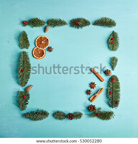 Christmas Frame made of Natural Fir Branch on Blue Background Christmas Food Decoration. Flat lay.