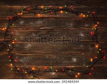 Christmas frame with Christmas lights and white snow on a dark wooden background. Holidays Concept. - stock photo