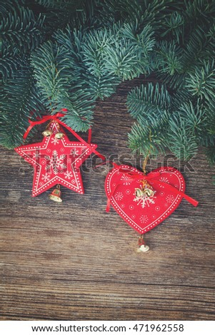 christmas fresh evergreen tree branches with red vintage heart and star decorations on wood, retro toned