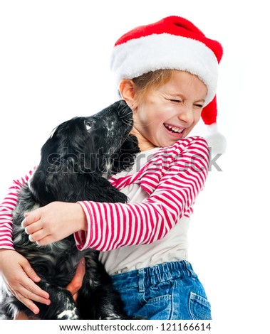 Christmas friends - little girl with cute puppy in a Santa hat - stock photo