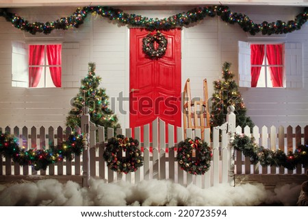 Christmas front door of a country house background. Decorated with lights front door of a pretty house with a white fence. Winter holidays concept.  - stock photo