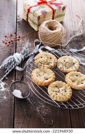 Christmas fruit mince pies and decorations over rustic wooden background - stock photo